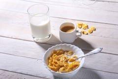 Corn- Flakesgetreide in einer Schüssel, im Glas mit Milch und in der Kappe mit Espressokaffee Morgenfrühstück Lizenzfreie Stockfotografie