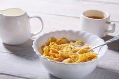 Corn- Flakesgetreide in einer Schüssel, im Glas mit Milch und in der Kappe mit Espressokaffee Morgenfrühstück Lizenzfreie Stockbilder