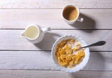 Corn- Flakesgetreide in einer Schüssel, im Glas mit Milch und in der Kappe mit Espressokaffee Morgenfrühstück Lizenzfreies Stockfoto