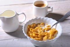 Corn- Flakesgetreide in einer Schüssel, im Glas mit Milch und in der Kappe mit Espressokaffee Morgenfrühstück Stockfotografie