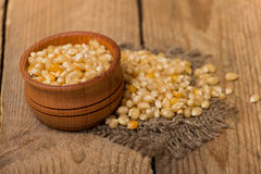 Corn grains. White corn grains in a pot on a wooden background Royalty Free Stock Image