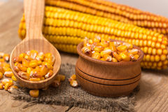 Corn grains. Yellow corn grains in a wooden pot on a wooden background Royalty Free Stock Photos