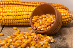 Corn grains. Yellow corn grains in a wooden pot on a wooden background Stock Photo