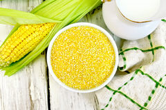 Corn grits in bowl on board top Stock Image