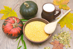 Corn grits, pumpkin and milk in a clay mug on a wooden table Royalty Free Stock Photo