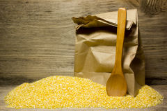 Corn grits. And wooden spoon on wooden background royalty free stock images