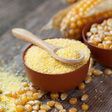 Corn groats in bowl, corn seeds and corncobs Stock Photo
