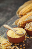 Corn groats and seeds in bowls, corncobs on background. Selectiv Royalty Free Stock Image