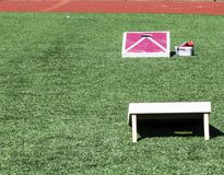 Corn hole game set up on turf field. Two red and white corn hole boards are set up on a green turf field across from each other stock photo