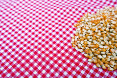 Corn kernels close up on a red and white tablecloth Stock Photos