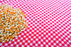 Corn kernels close up on a red and white tablecloth Royalty Free Stock Photo