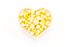 Corn kernels in a heart shaped white bowl, on white Royalty Free Stock Image