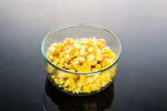 Corn kernels in transparent glass bowl in dark background Royalty Free Stock Photos