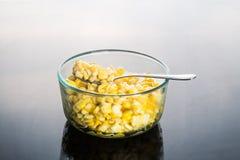 Corn kernels in transparent glass bowl  in dark reflective backg Royalty Free Stock Images