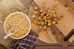 Corn kernels in wooden plates and popcorn with Caramel and almon Stock Photos