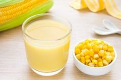 Corn milk in glass, kernel corn in bowl and fresh corn Stock Image