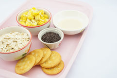 Corn, oats, chocolate, cracker and sweetened condensed milk on pink tray Stock Images
