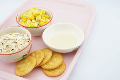 Corn, oats, cracker and sweetened condensed milk on pink tray. Corn, oats, cracker and sweetened condensed milk placed on pink tray with white background Royalty Free Stock Images