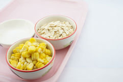 Corn, oats and sugar on pink tray. Corn, oats and sugar placed on pink tray with white background Royalty Free Stock Images