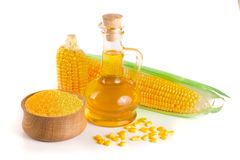 Corn oil in decanter, fresh corn cobs and cornmeal isolated on white background. Corn oil in decanter, fresh corn cobs and grains isolated on white background Stock Photos