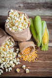Corn and popcorn in rustic version. On old wooden table Royalty Free Stock Photography