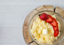 Corn porridge with strawberries - breakfast served on natural sawed wood Stock Images