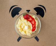 Corn porridge with strawberries in shape of alarm clock, breakfast time concept Royalty Free Stock Image