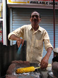 Corn Preparation. A poor man from India preparing a corn dish on his cart which is actually a street side restaurant. Seen is the movement of his hand, where he Stock Photography