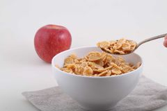 Corn and rice flakes in a spoon and a red apple on a white backg Stock Photos