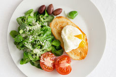 Corn salad dressed with olive oil and lemon juice sprinkled with parmesan,  poached egg toast, fresh tomato, and kalamata olives Stock Photo