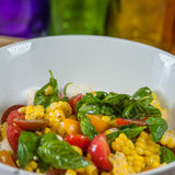 Corn Salad. Fresh summer corn salad, made with cherry tomatoes, corn from the cob and bright pieces of basil Stock Photos