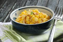 Corn Salad. A small bowl of corn salad, underlined with a kitchen towel, laid on a rustic wooden table stock photography