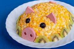 Symbol of the new 2019. Salad in the form of a cute pig on a blue background. Corn salad in the style of the New year - the year of the yellow pig. Symbol of the royalty free stock photos
