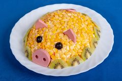 Symbol of the new 2019. Salad in the form of a cute pig on a blue background. Corn salad in the style of the New year - the year of the yellow pig. Symbol of the stock image