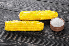 Corn and salt on a wooden table Royalty Free Stock Photos