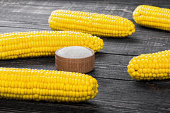 Corn and salt on a wooden table Stock Photography