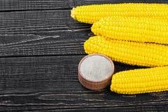 Corn and salt on a wooden table Stock Photos