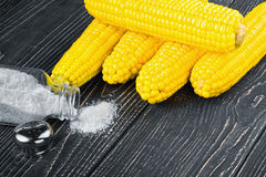Corn and salt on a wooden table Stock Images