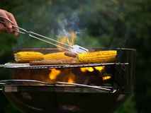 Corn and sausages on a flaming barbecue. Nice filled flaming barbecue with sausages and corn Royalty Free Stock Photography