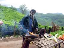 Corn seller. An old men selling roasted corn on roadside on the hills of kerala,india Royalty Free Stock Image