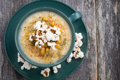 Corn soup with popcorn in cup on wooden table, top view Stock Images