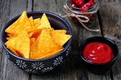 Corn Tortilla Chips or Nachos with tomato sauce on wooden table Royalty Free Stock Photos
