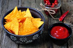 Corn Tortilla Chips or Nachos with tomato sauce on wooden table Stock Images