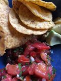 Corn tortilla chips, salsa, avocado. Mexican food that spicy and delicious, fresh tomato salsa with cilantro, served with yellow corn tortilla chips and avocado Stock Photos
