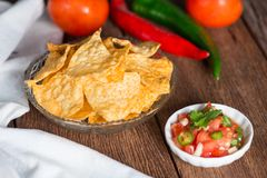 Corn tortilla chips with tomato salsa. Royalty Free Stock Images