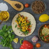 Corn tortilla prepared Mexican tacos. The view from the top. Cake made of cornmeal with ground beef and vegetables Mexican tacos on a wooden table. Ingredients Royalty Free Stock Image