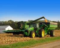 Corn tractor. Combine and tractor harvesting corn stock photos