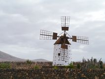A corn wind mill on Fuerteventura. Historic wind mill in the surroundings of El Cotillo on the Spanish island Fuerteventura one of the Canary islands in the Royalty Free Stock Image