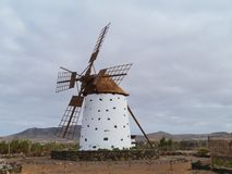 A corn wind mill on Fuerteventura. Historic wind mill in the surroundings of El Cotillo on the Spanish island Fuerteventura one of the Canary islands in the Stock Photography