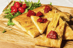 Cornbread on a wooden board with dried tomato and cherry tomatoe Stock Photos